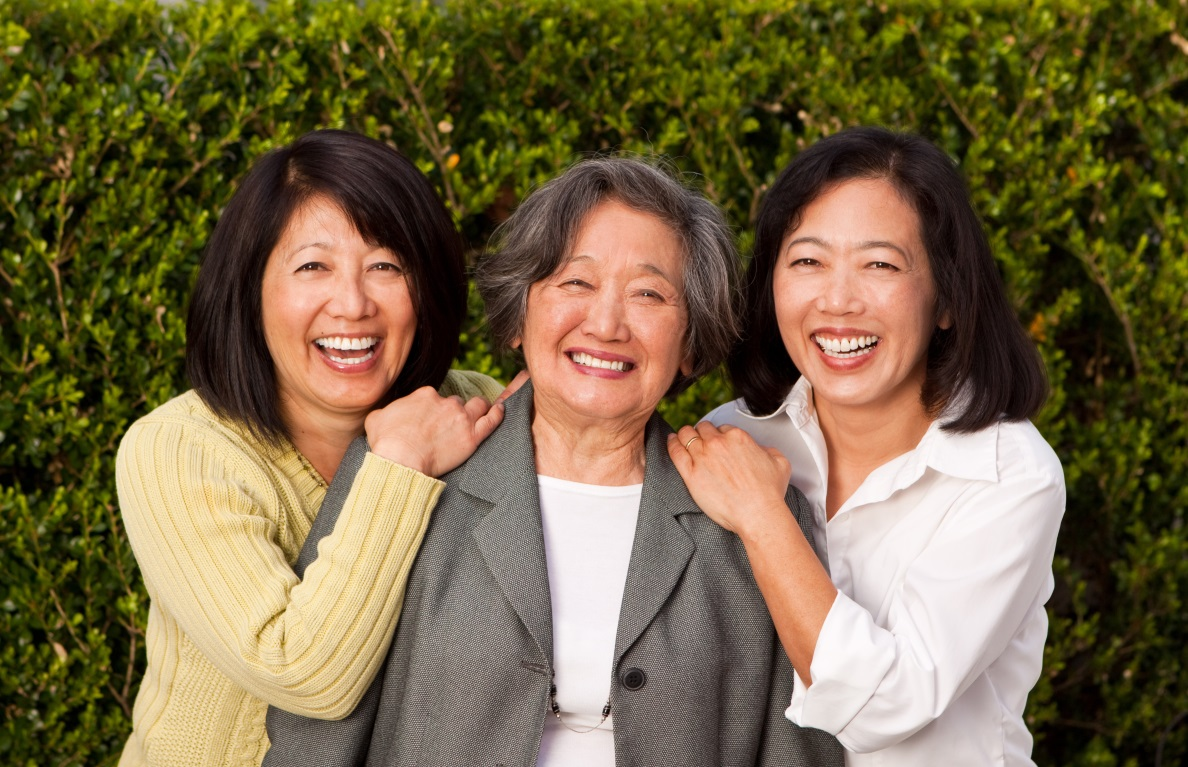 An elderly mother with her two adult daughters, smiling outdoors in front of a green hedge.