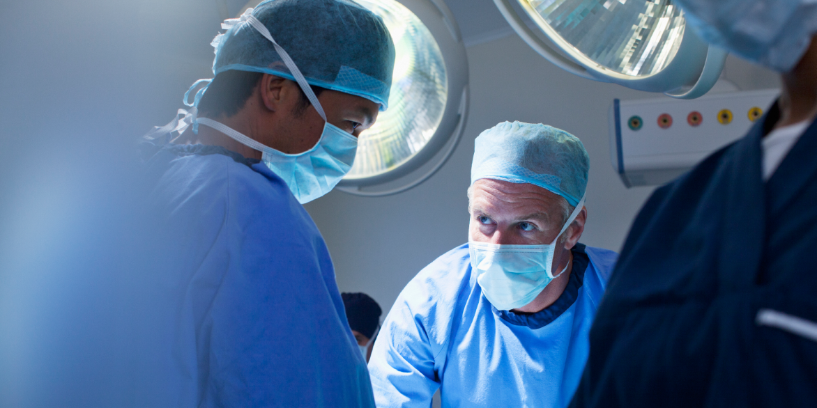 Two male healthcare providers in an operating room setting.