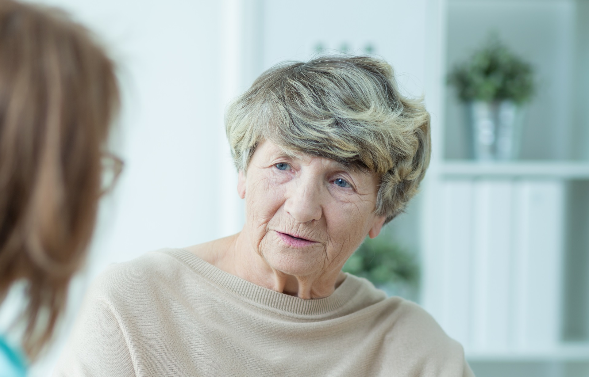 An elderly woman engaged in serious conversation with a female healthcare provider inside a home setting.