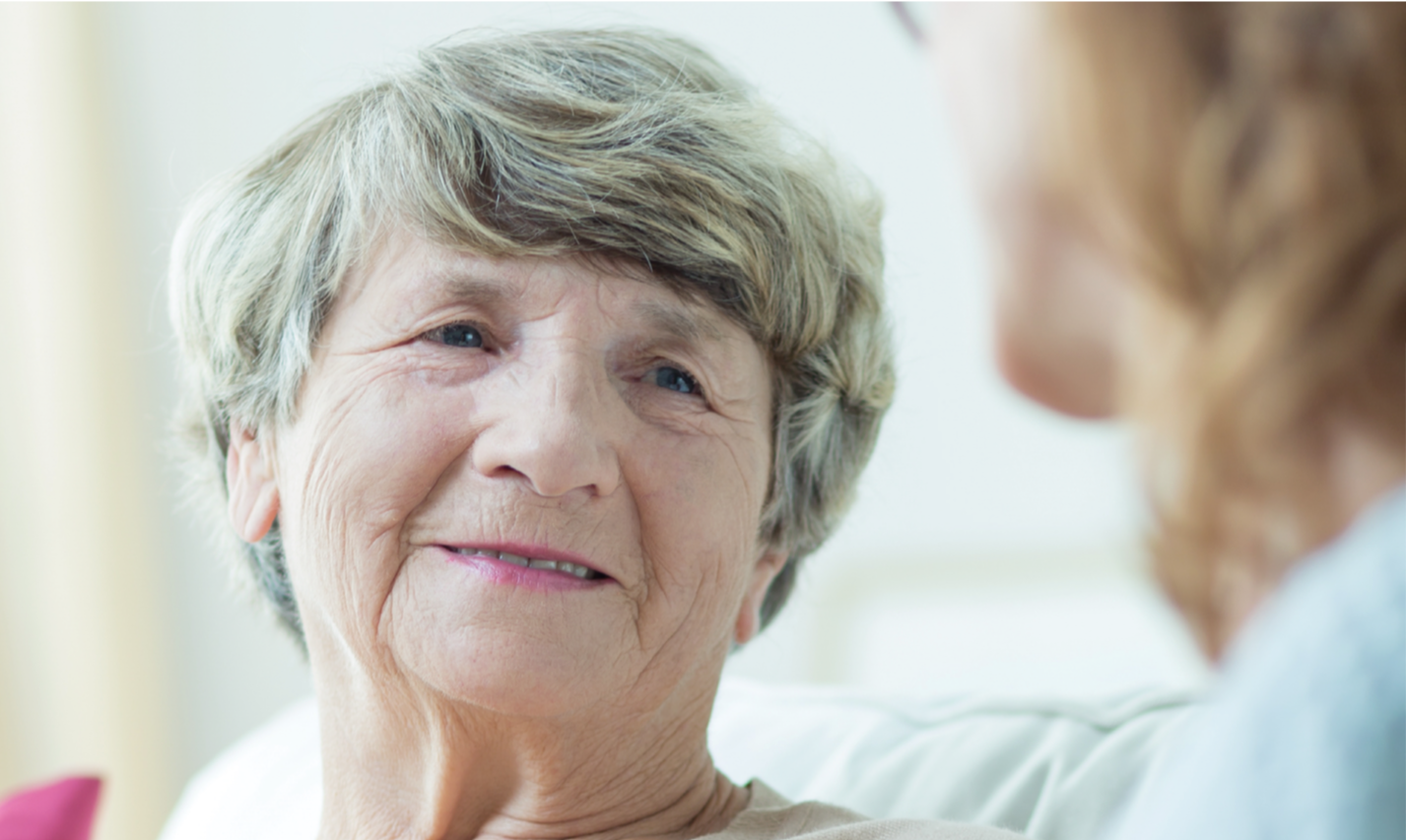 Elderly woman smiling in conversation with another woman