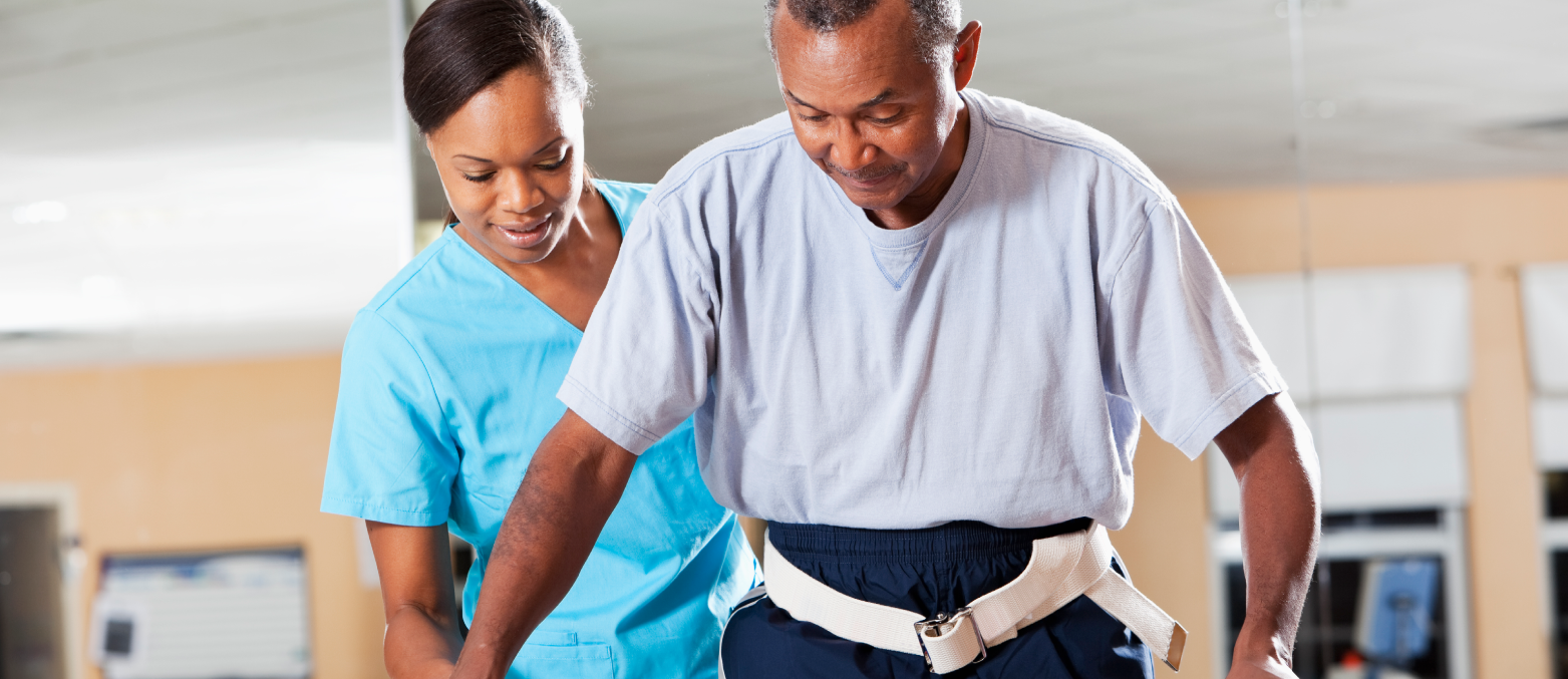 Healthcare provider assisting patient to walk through rehabilitation.