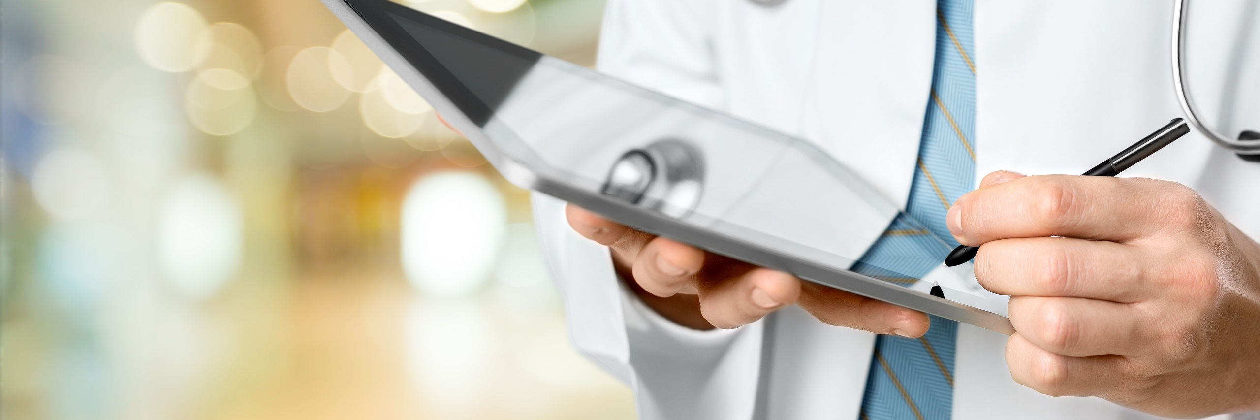 Health care provider holding a tablet and stylus pen.