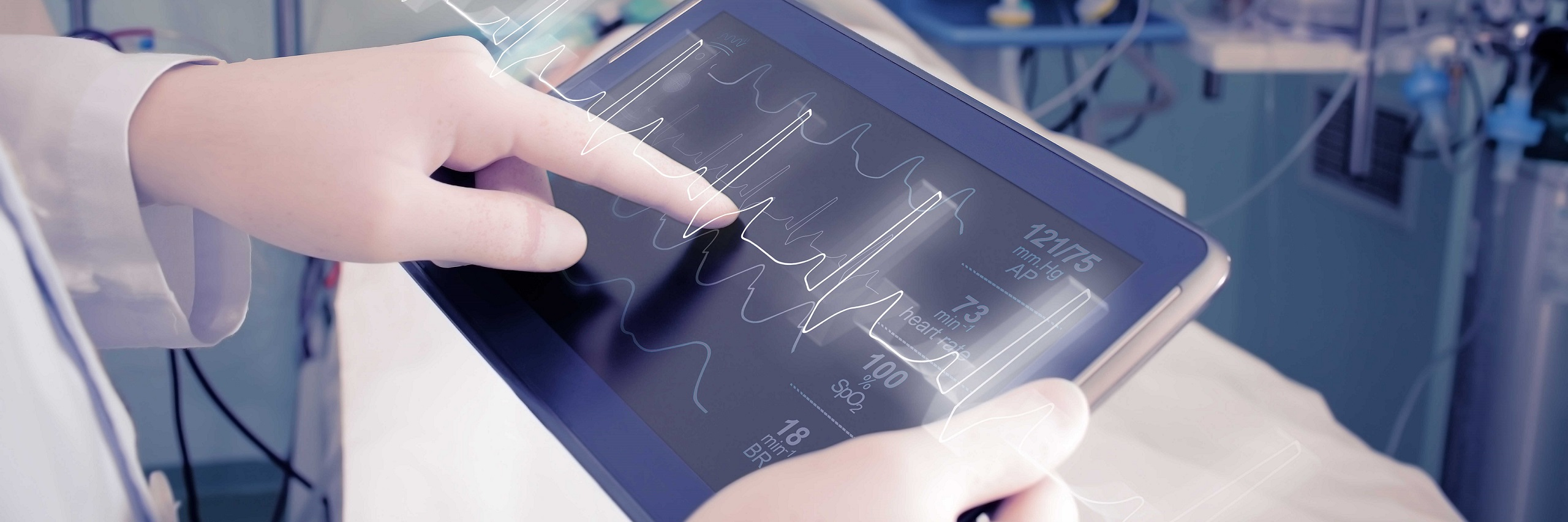 Healthcare provider pointing to a tablet monitoring a heartbeat.